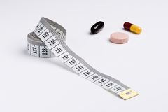 Isolated measure tape and pills. Measure tape and some medicinine pills Royalty Free Stock Images