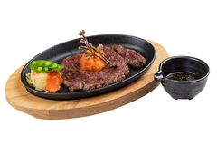 Isolated medium rare wagyu steak topping with mince carrot on hot plate and wooden plate served with potato salad with ponzu sauce