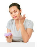 Middle Age Asian Woman apllies cream on her face. Stock Photos