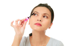 Isolated middle age asian woman with mascara brush Stock Photos