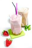 Isolated milkshakes. Strawberry and chocolate milkshakes with fresh strawberries Royalty Free Stock Photos