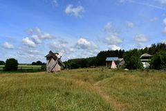 An abandoned wooden windmill in the vast green field near the forest. Barns and other constructions stand next stock photo