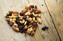 Isolated mixed nuts and dried fruits in the heart shape on the rustic background Royalty Free Stock Images