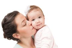 Mother kissing her baby girl Isolated on white bac. Isolated mother kissing her baby girl on white Royalty Free Stock Images