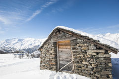 Isolated mountain hut in the snow Stock Photos
