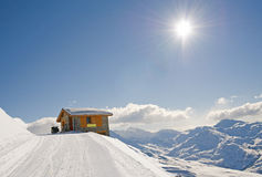 Isolated mountain hut in the sun. Mountain hut on edge of mountain with landscape view and a skidoo bike stock images