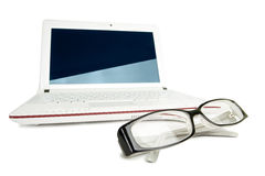 Isolated netbook with glasses Royalty Free Stock Images