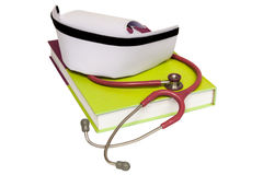 An isolated nurse hat. On textbook and stethoscope royalty free stock images
