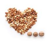 Isolated nuts heart shape and three dots. Isolated almonds, cashew, hazelnut heart shape and three dots Stock Photos