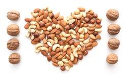 Isolated nuts heart shape and walnut raw. Isolated almonds, cashew, hazelnut heart shape and walnut raw Royalty Free Stock Photo