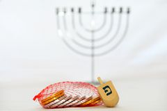 Isolated Obejects for Hanukkah. Photo of a dreidel (spinning top), gelts (candy coins) and a silver menorah for Hanukkah, isolated on white Stock Photo