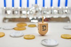 Isolated Obejects for Hanukkah. Photo of a dreidel (spinning top), gelts (candy coins) and a silver menorah for Hanukkah, isolated on white