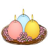 Isolated object on white background Easter candles in the shape of an egg. Three pieces of different colors with fire. In a basket nest and flowers. Color Royalty Free Stock Photos