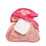 Isolated objects: bag with gift tag. Ladies toiletry/beauty products bag on white background. Space for copy on the tag Royalty Free Stock Photos