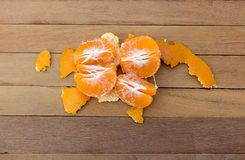 Isolated Orange being peeled on the wooden floor. Stock Image