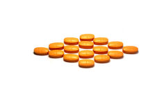 Isolated orange pills. Isolated orange tablets ordered as rhomb Royalty Free Stock Photography