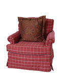 Isolated Overstuffed Chair. A coral colored plaid overstuffed armchair with a paisley pillow isolated on white Stock Image