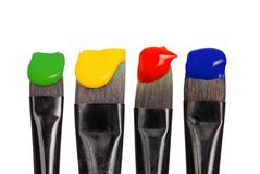 Isolated paintbrushes with paint. Four paintbrushes with vibrant paint, isolated on pure white background royalty free stock images