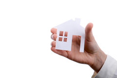 Isolated paper house in hand. Hand holding an isolated paper house with a white background Royalty Free Stock Photography