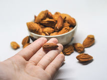 Isolated peeled and unpeeled almond on hand,floor and in ceramic bowl. Isolated image of peeled and unpeeled almond on someone's hand also scattered on the Stock Photo