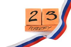 Isolated perpetual wooden calendar with date of February 23 and ribbon tricolor Russian flag on white background with copy space. Concept of Defender of the royalty free stock photo
