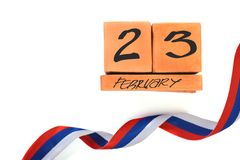 Isolated perpetual wooden calendar with date of February 23 and ribbon tricolor Russian flag on white background with copy space. Concept of Defender of the stock photos