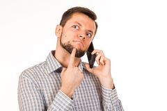 The bearded man is talking on the phone. Posing with different emotions. Simulation of conversation. stock photos