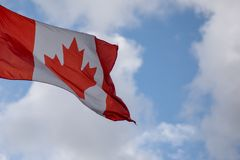 Isolated photograph of canadian flag with white fluffy clouds in background stock image