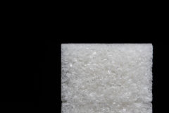 Isolated piece of sugar on a black background. Macro Stock Photography