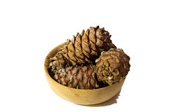 Isolated pile of conifer cones in wooden bowl. Pile of conifer cones placed in wooden bowl isolated on white background Stock Photo