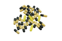 Isolated Pills. Medicine dark green and yellow capsules on white background. Pharmacy pills close up view Royalty Free Stock Images
