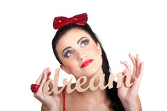 Isolated pin up woman with a dream in grasp. Isolated woman holding the words dream in hands looking to empty copyspace. Pin up your goals and dreams Royalty Free Stock Image