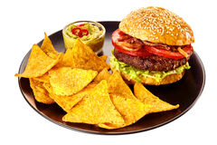 Isolated plate of chips, guacamole and burger Royalty Free Stock Photos