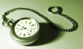 Isolated pocket watch with a chain, tinted green. Isolated old silver pocket watch; focused on the dial; with a chain, tinted green; gradient background. I would royalty free stock photography