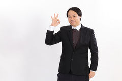 Isolated Portrait of an Asian business man gesturing OK Royalty Free Stock Images