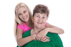 Isolated portrait of blond granddaughter hugging her grandmother Stock Images