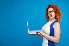 Isolated portrait of a business girl holding a laptop. on a blue background. The girl looks surprised and confused. Place for text. Business and emotional Stock Image