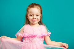 Baby girl in beautiful pink dress on blue isolated stock images