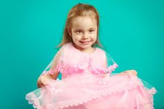 Baby girl in beautiful pink dress on blue isolated royalty free stock images