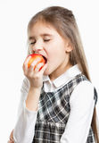 Isolated portrait of cute brunette schoolgirl biting red apple Stock Photo