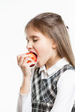 Isolated portrait of cute schoolgirl biting red apple Stock Image