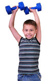 Isolated portrait of elementary age boy with dumbbells exercising Royalty Free Stock Photography
