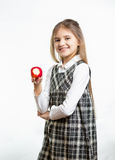 Isolated portrait of happy girl in school uniform holding apple Royalty Free Stock Photography