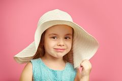 Isolated portrait of little girl in panama hat, smile, holds hand hat, stands on pink isolated background. stock images