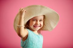 Isolated Portrait Of Little Girl In Panama Hat, Smile, Holds Hand Hat, Stands On Pink Isolated Background. Stock Photos