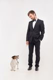 Isolated portrait of owner with his dog. Young man and his dog in front of white background. He keeps the dog on the leash Royalty Free Stock Photography