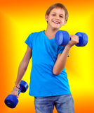 Isolated portrait of smiling kid exercising with dumbbells Stock Photography