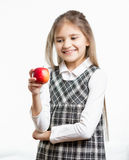 Isolated portrait of smiling schoolgirl looking at apple Stock Image