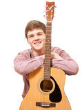 Isolated portrait of smiling young man leaning against guitar Royalty Free Stock Image
