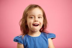 Isolated portrait of surprised girl three years old on pink isolated background. Small child expresses sincere emotions. Of astonishment and amazement, opens stock photography